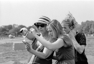 Two  sighted students help a blind photographer adjust her camera to take a picture in Berlin. (Photo credit: Stephan Wilke)