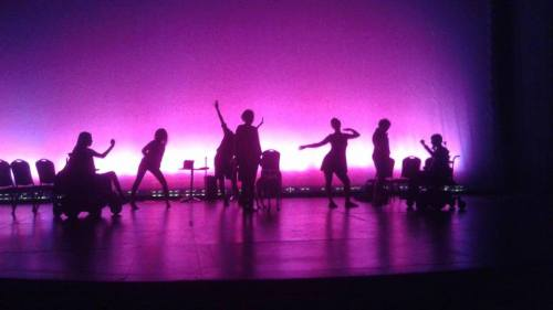 Seven dancing human silhouettes and one dog silhouette pose against a bright violet background.
